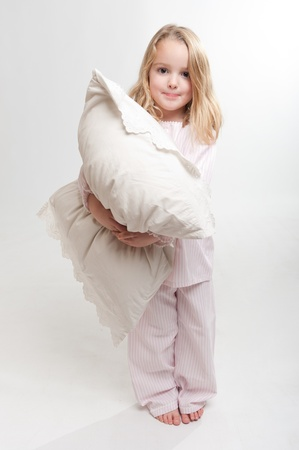 nightdress:   Cute little blonde girl in her pajamas holding a pillow