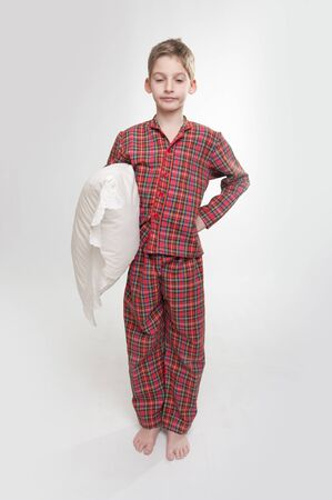 closed eyes: Jongetje met gesloten ogen in pyjama met een kussen Stockfoto