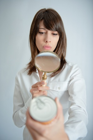 sodium:   Young woman inspecting a can�s nutrition label with a magnifying glass   Stock Photo