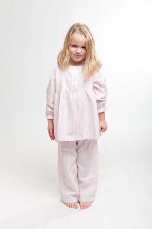 Cute little blonde girl with an angry expression in her pajamas  photo