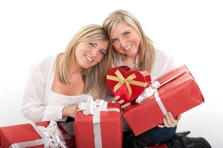 Two young sisters surrounded by gift boxes, some of them heart shaped  Stock Photo - 10601723