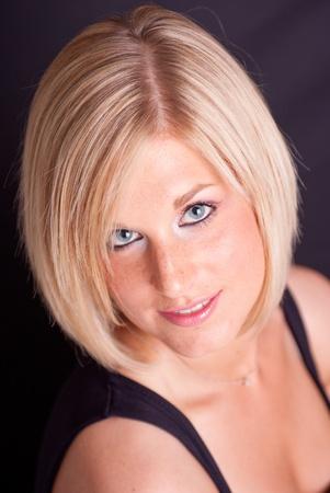 blonde yeux bleus: Close-up portrait d'une jolie femme blonde sur un fond noir