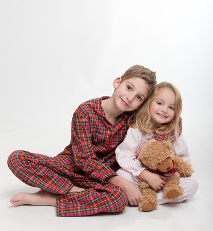 little girl barefoot:  Little boy and girl in their pajamas with a teddy bear