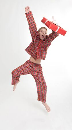 Young boy in pajamas happily jumping holding a gift photo