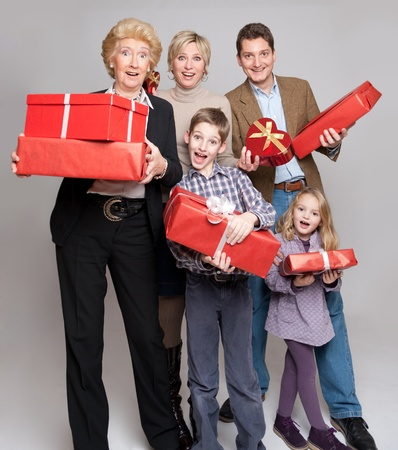 Happy family members holding gift boxes in different shapes photo