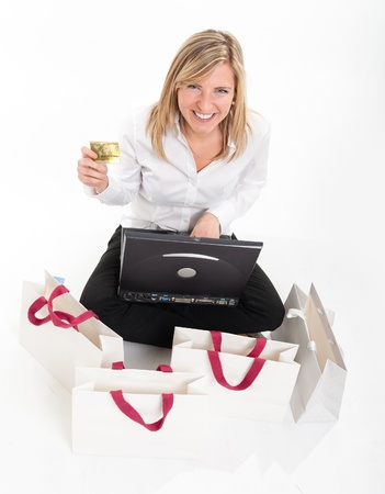 Exstatic young blond woman holding a credit card in front of a computer surrounded by shopping bags Stock Photo - 10623539