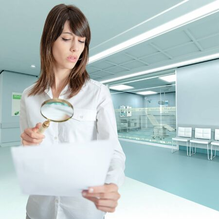 admissions:   Young woman at the hospital examining a document with a magnifying glass   Stock Photo