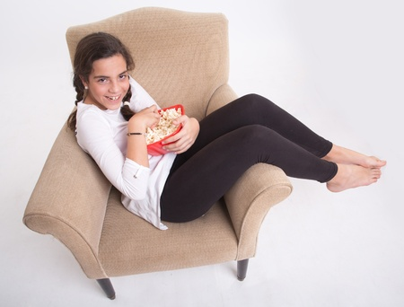 young girl barefoot:  Smiling Girl sitting on an armchair with a popcorn bowl