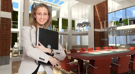 cor:  Young woman holding a laptop in the boardroom of a modern office   Stock Photo