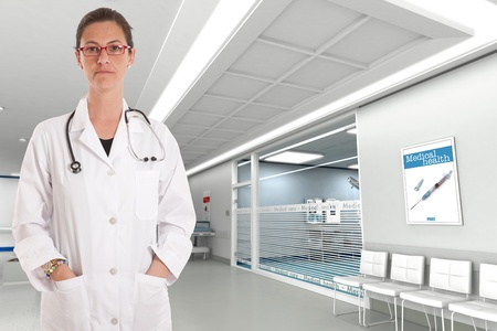 hospital staff:   Serious female doctor standing in a hospital interior