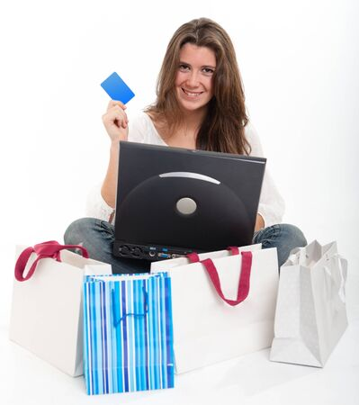 Young brunette holding a card using her computer surrounded by shopping bags Stock Photo - 10601581