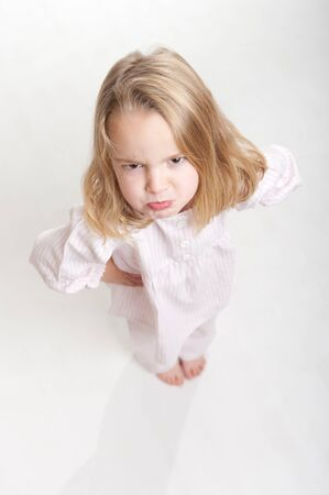 nighttimes:  Aerial view of a cute little blonde girl with an angry expression in her pajamas  Stock Photo