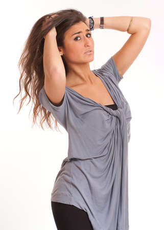 tunic:  Attractive young brunette arranging her hair