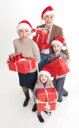 Happy family with two kids wearing Santa  hats carrying presents  photo