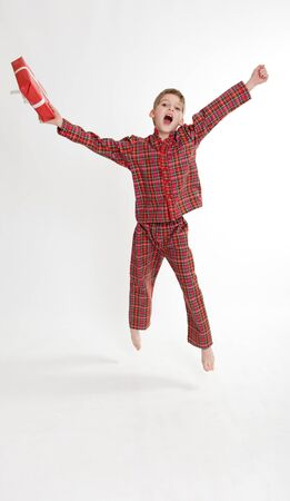 in pajama:  Young boy in pajamas happily jumping holding a gift