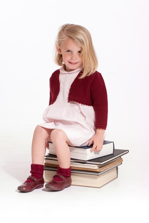cute little girl smiling:  Cute little girl sitting on a pile of books   Stock Photo