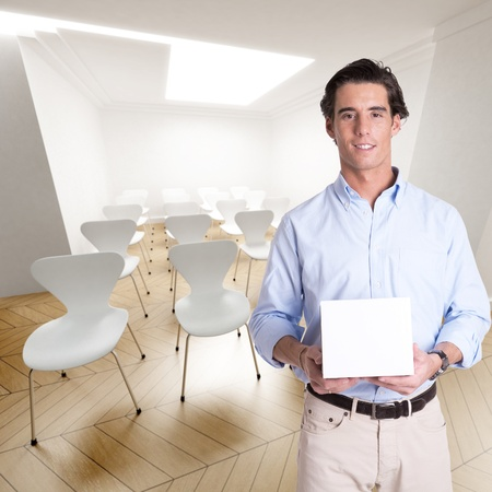 lecture hall:  Cheerful young man holding a white box in a conference room
