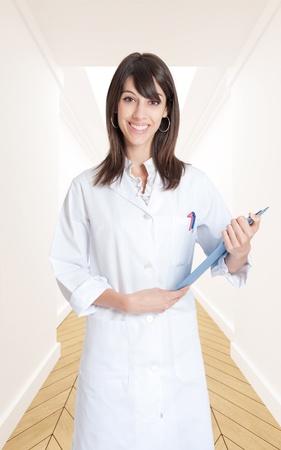 Smiling nurse holding a folder in a corridor  photo