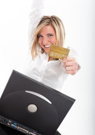Portrait of an ecstatic young blonde holding a credit card in front of a laptop   Stock Photo - 10645285
