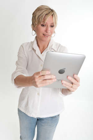 palmtop:   Blonde woman using a PC tablet with an amused expression   Stock Photo