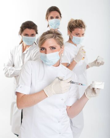 latex girl:   Four female dentists posing with masks and equipment