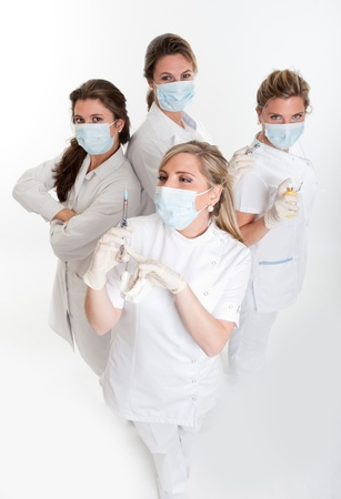 hygienist:    Four female dentists posing with masks and equipment