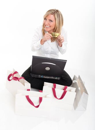 Happy young blonde showing her credit card sitting in front of a laptop surrounded by shopping bags Stock Photo - 10743613