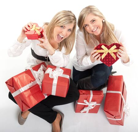 18 19:  Two young sisters surrounded by gift boxes, some of them heart shaped  Stock Photo