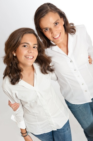 Mom and young teenage daughter holding each other smiling looking at the camera   photo