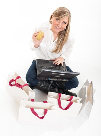 Aerial view of a young brunette holding a card using her computer surrounded by shopping bags Stock Photo - 10743611
