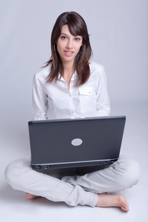 Barefoot young woman using her computer cross-legged on the floor    Stock Photo