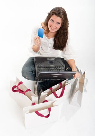 Aerial view of a young brunette holding a card using her computer surrounded by shopping bags   Stock Photo - 10769181
