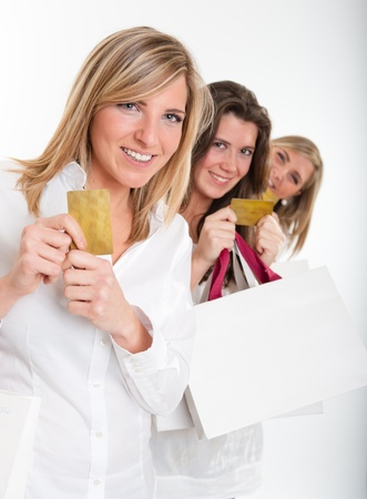 Three young women with happy expressions with credit cards holding lots of shopping bags Stock Photo - 10761486