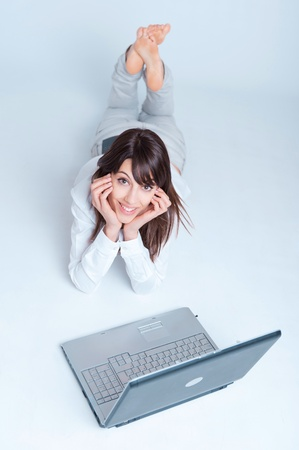 Young woman using a laptop computer on the floor    Stock Photo - 10769170