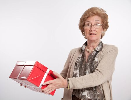 Surprised elegant mature woman holding a red gift box  photo