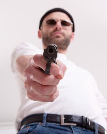 Dangerous looking man holding a gun aiming at you  photo