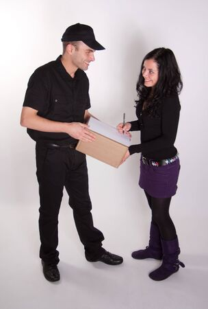 Messenger delivering a parcel to an attractive brunette Stock Photo - 10893727