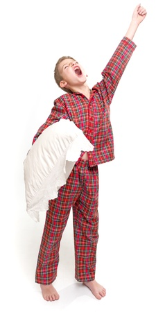 pajama:   Yawning boy in pyjamas holding a pillow    Stock Photo