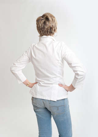 woman back view:   Rear view of a woman looking at something with hands on her hips   Stock Photo