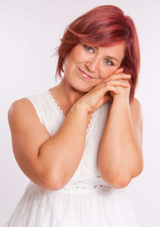 red head woman:  Portrait of a red head woman in a white dress with a dreamy expression  Stock Photo