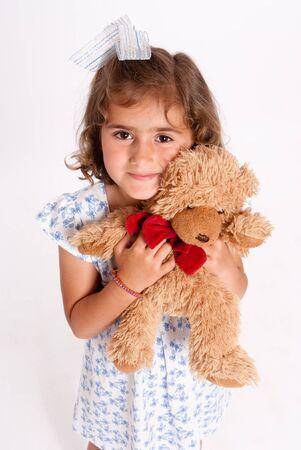 Little girl lovingly holding a teddy bear  photo