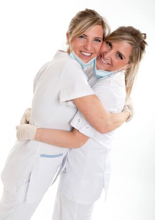 Two young women in medical attire hugging   photo