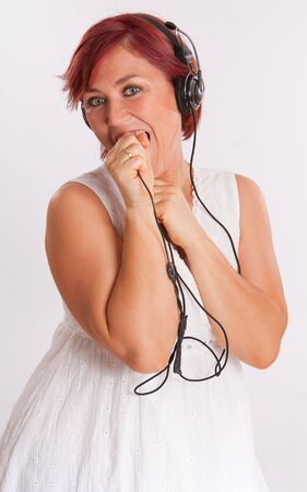 enraptured: Smiling red headed woman wearing headphones  Stock Photo