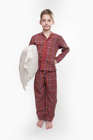 Little boy in pyjamas holding a pillow