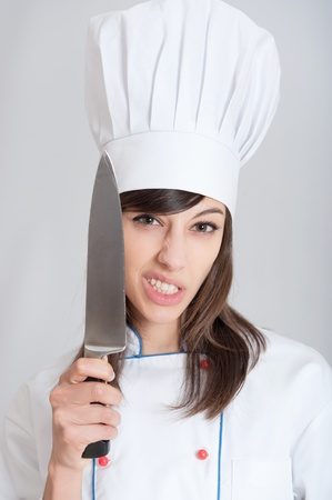 holding a knife:   Young female chef holding a knife with a menacing expression   Stock Photo