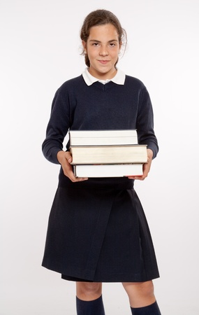 schoolgirls:  Schoolgirl carrying three heavy books  Stock Photo