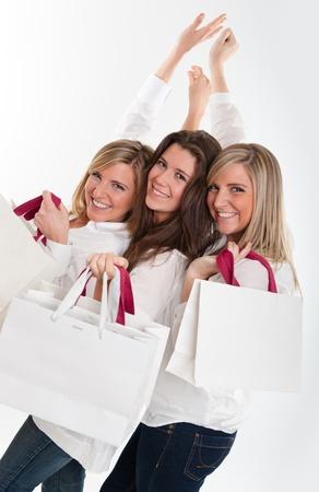 Tres mujeres jóvenes con las expresiones felices sosteniendo un montón de bolsas de la compra