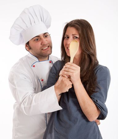 kitchen spanish:  A professional chef and a young woman fighting for the possession of a wooden spoon  Stock Photo