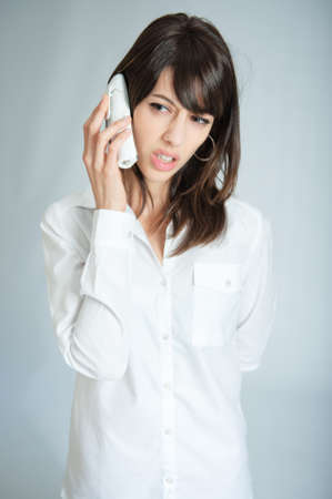 Young brunette talking on the phone with an annoyed expression  photo