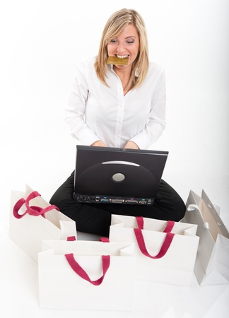 Happy young blonde biting her credit card sitting in front of a laptop surrounded by shopping bags Stock Photo - 11036627